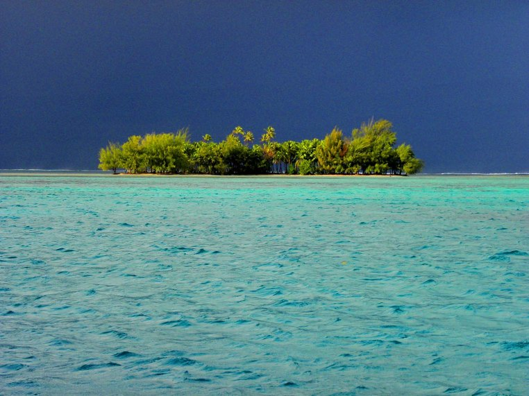 Motu (islet) on the lagoon's exterior reef, a rain squall passing to leeward. Raiatea, Fenua, French Polynesia